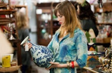 A woman is in an antique store looking at a Ming vase.