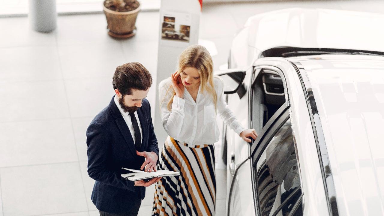 A salesperson and a customer discuss a car