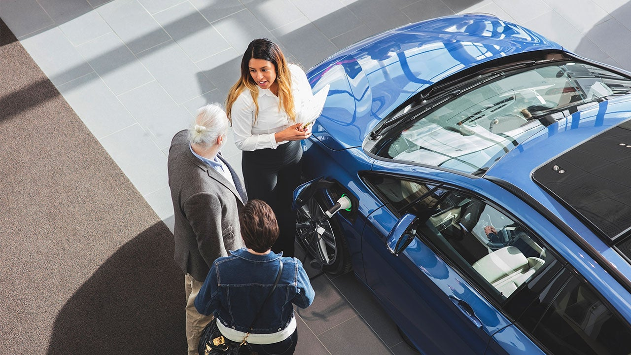 Car dealer talking with customers