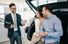 Couple listens to sales pitch in car showroom