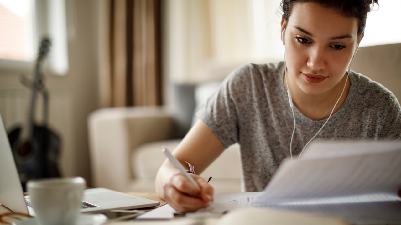 Woman at a desk writing financial payment plan