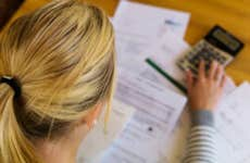Woman looks through paperwork with a calculator