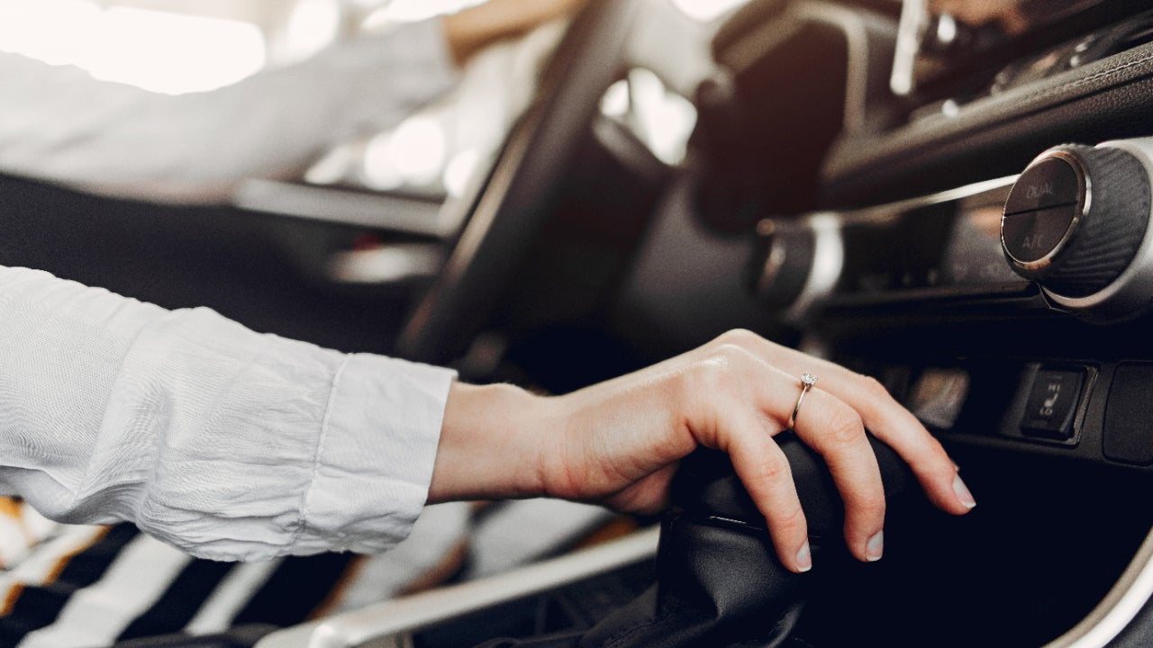 A woman's hands on a car's steering wheel and gear shift