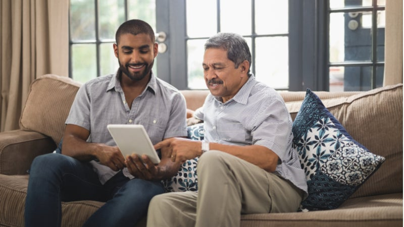 Older man helps young man using tablet