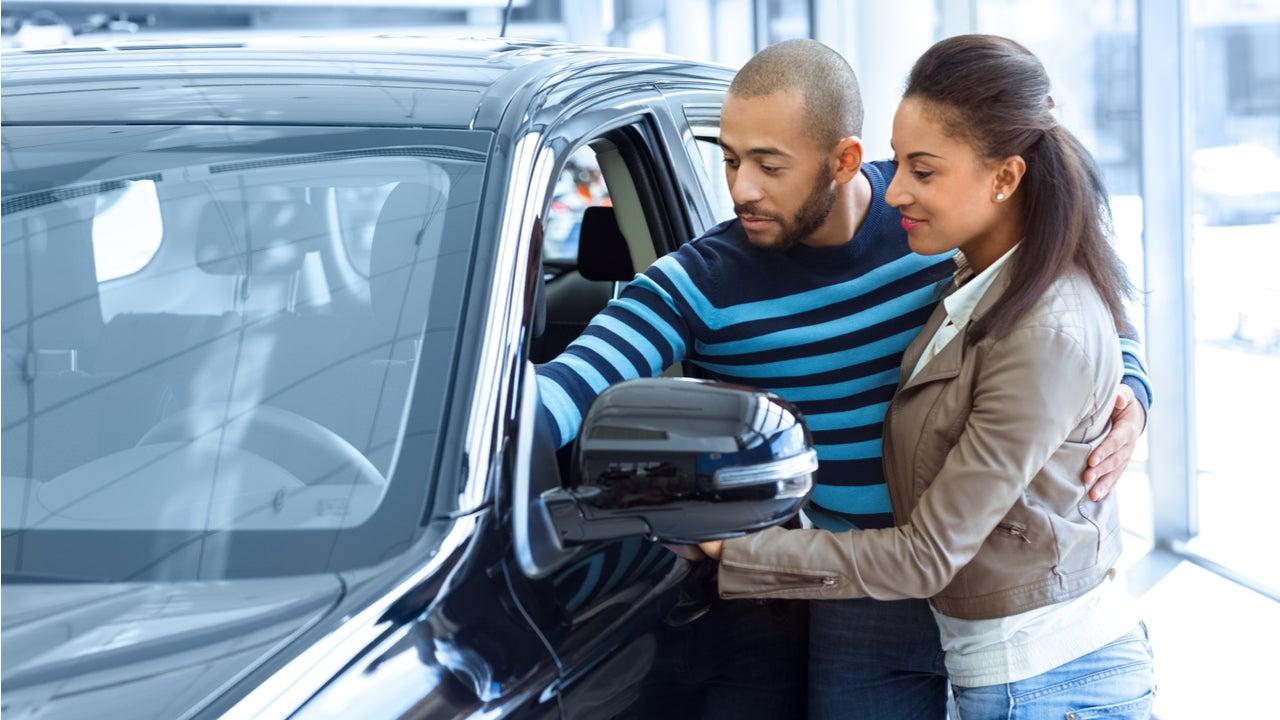 Couple look at a car at a dealership