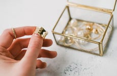 A woman holds a gold ring in front of a jewelry box