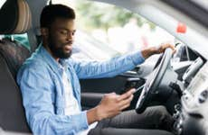 Man checks phone while sitting in car
