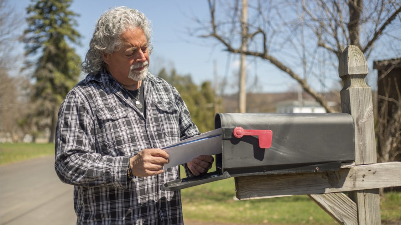 Man looking at mail by the mailbox.