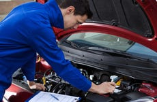 Mechanic looks under the hood of a car