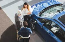 Couple looks at a car at a car dealership