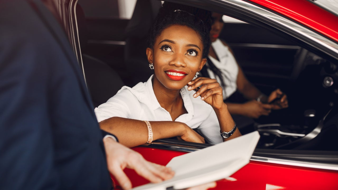 Two women sit in a red car at a dealership.