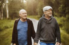 An elderly gay couple walks together on a nice, scenic forest road.