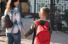 Mother walks a child to first day of school