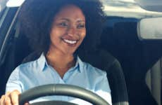 Woman smiles while driving a car