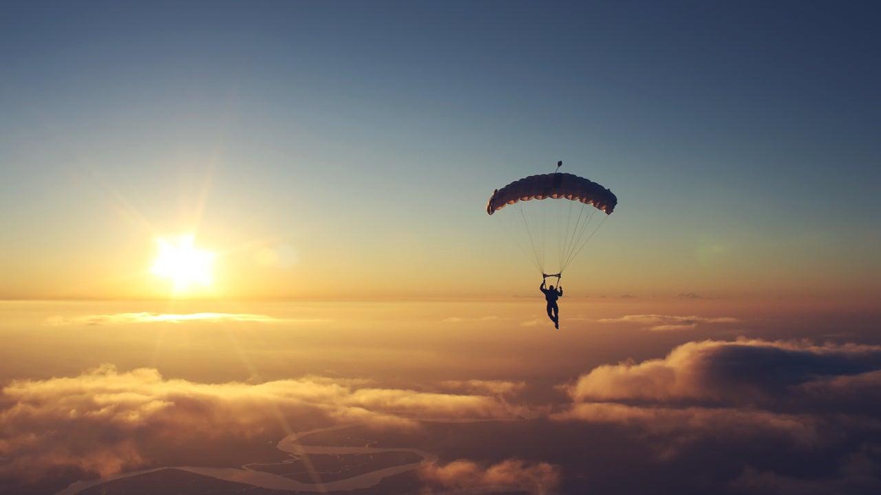 A man parasailing into the sunset.