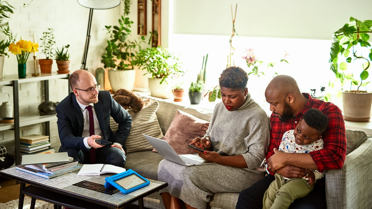 A couple and their child review their finances with a consultant.