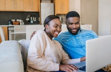 Young couple work together on laptop in apartment