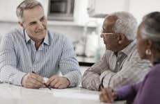 A financial advisor sitting down with an older couple.