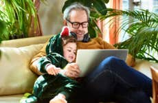 Father and son (who is dressed like a dinosaur) sit on the couch in front of a laptop looking at funny viral videos.