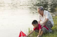 Asian grandfather and son hang out by the lake and put a toy sailboat into the water.