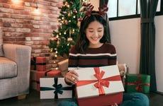 Young Asian woman opens Christmas gift box
