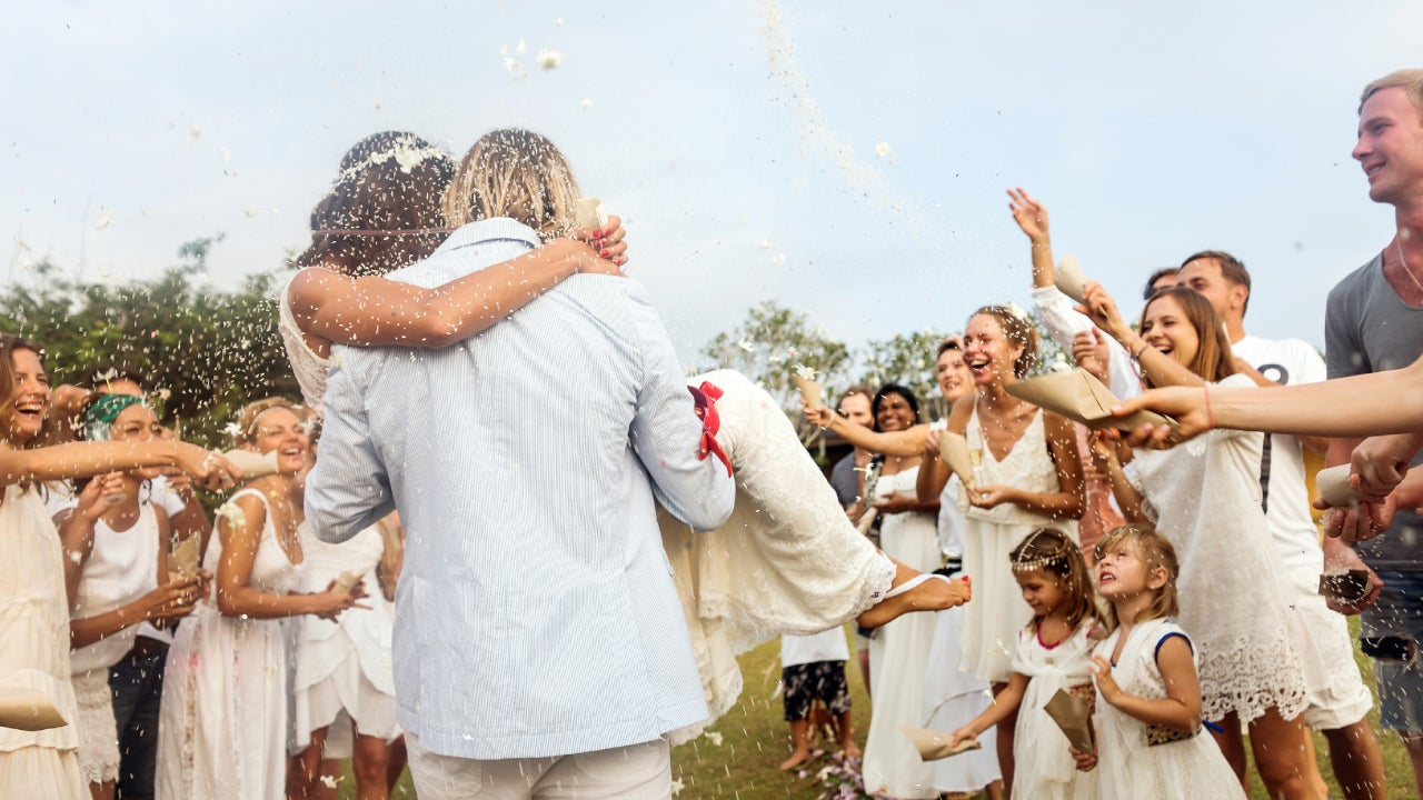 The back of a groom carrying his bride at an outdoor wedding while attendees throw rice!