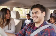 A man drives his family on a trip in their van; everyone is smiling and having a great time!