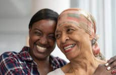 A mother and daughter smile together for a picture. The mother is wearing a silk scarf over hear head as she is undergoing chemotherapy.