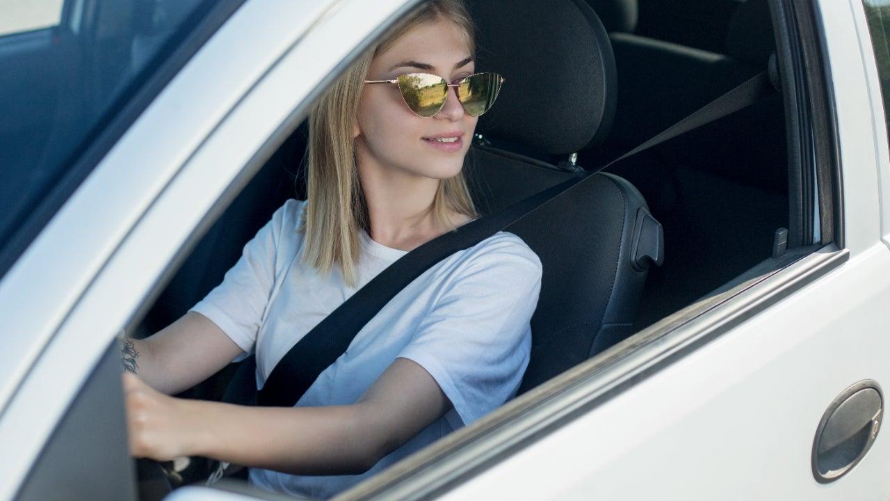 A woman wearing sunglasses looks out an open car window.