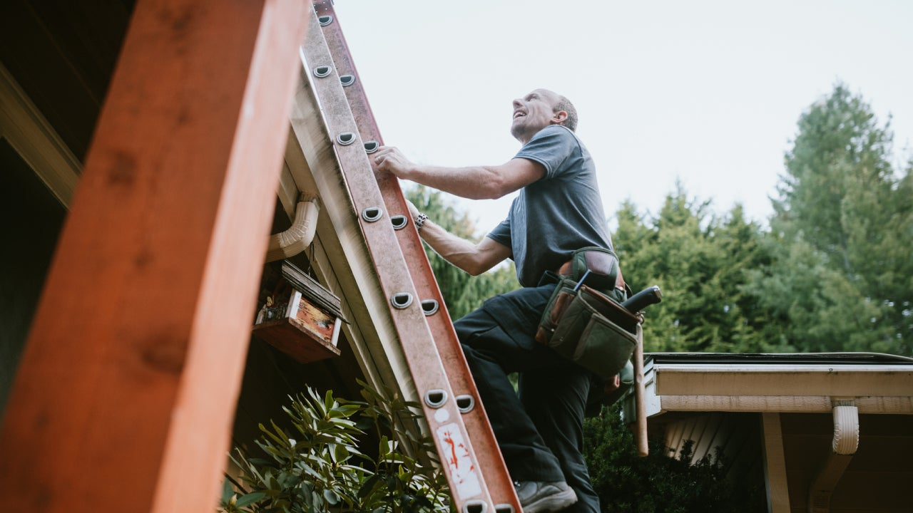 A man on a ladder climbing up to the roof.