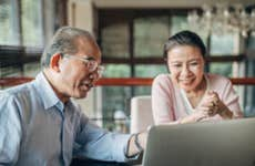 Asian couple is sitting in front of a laptop and looking at various financial options when converting their term life insurance.