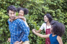 Joyful, interracial family with two children enjoying a day together in the park.