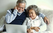Loving Asian elderly cheerful couple using laptop computer in bed.