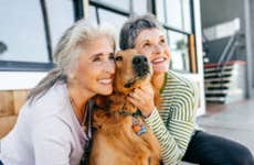 Two older ladies pose for a picture next to their golden retriever.