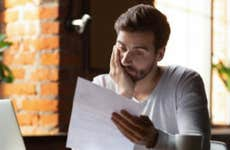 Man looking stressed while reading financial documents.