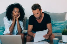 A stressed out woman and man look over bills while sitting on a couch.