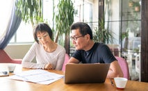 Older Asian couple sits at the kitchen table going over their finances.