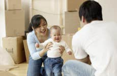 A man and woman play with their small child after a hard day of moving boxes into a new home.