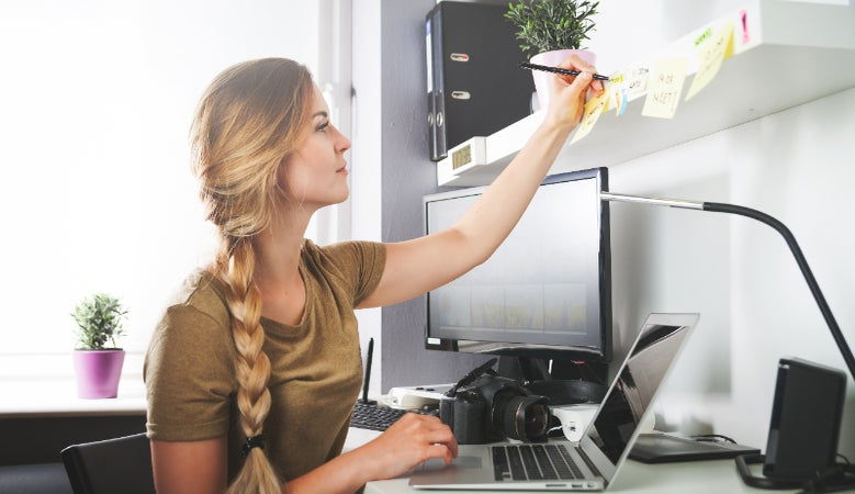 Young woman marking post-it notes in home office