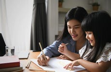 Mother working from home coloring with young daughter