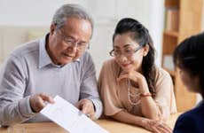An Asian couple reviewing their options with a financial advisor after their death benefits policy has been denied.