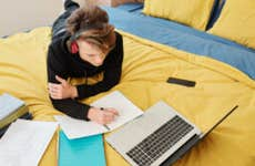 High school student studies on a bed