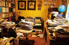 A work area or den that is full of papers and clutter.