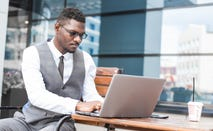 Man works on investing on laptop