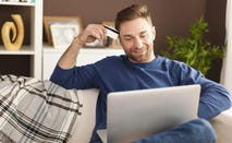 Man pulls out credit card while online shopping