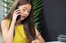 Woman speaks on the phone while doing paperwork