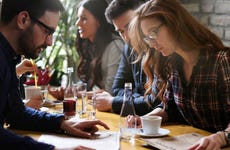 Young people looking at menu in restaurant