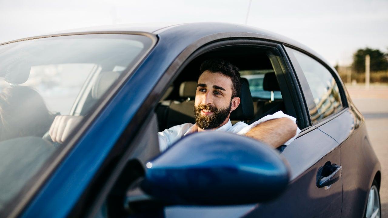 A man drives a blue car.