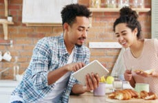 Young couple looks at shopping deals on tablet over breakfast