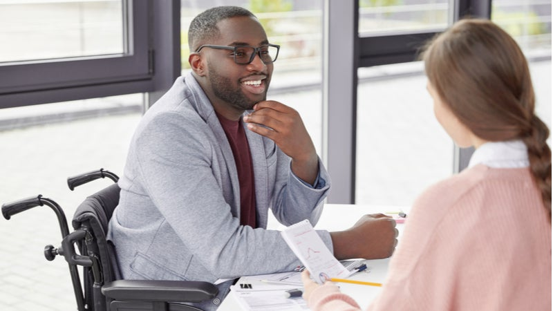 Man in wheelchair discussing paperwork with colleague